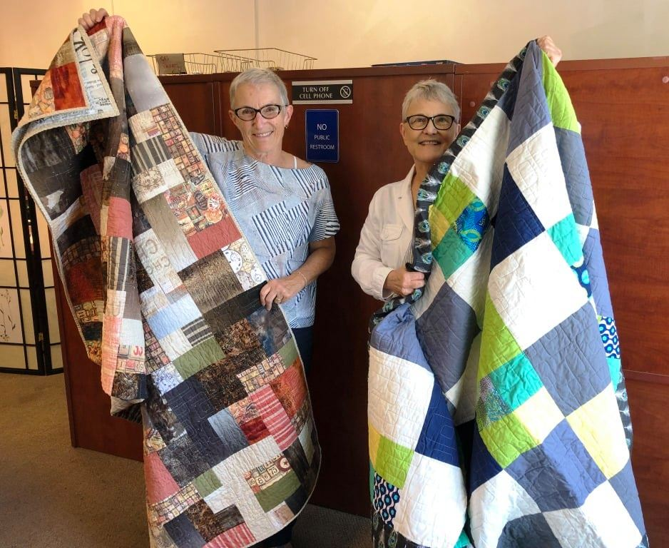 Two women hold up donated handmade quilts.